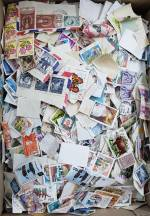 Accumulation of Australian and Foreign stamps on and off paper in small box.